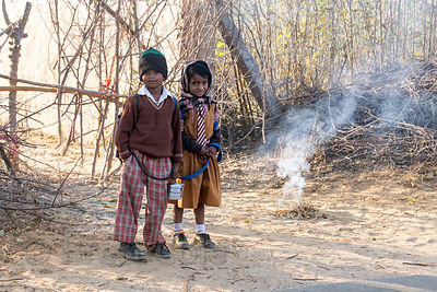Children warm by a fire of small sticks on a cold winter morning as they wait for the school bus, Nedaliya, near Pushkar, Rajasthan, India