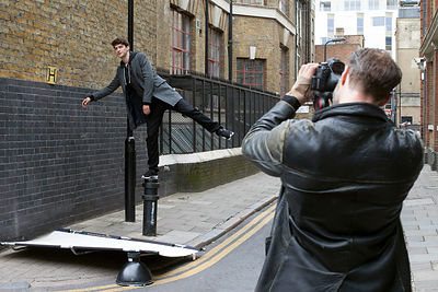UK - London - A photographer shoots a model as he balances on a bollard during a fashion shoot in the streets of Shoreditch