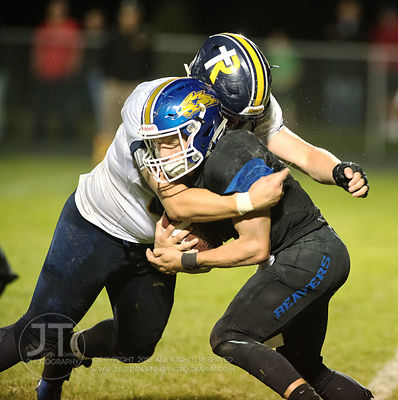 Wilton's Jerome Mays (1) gets tackled by Iowa City Regina's Cole White (50) during the second half of play in Wilton on Frida...