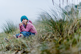 Little Danish girl in a blue hat at the beach in autumn 1