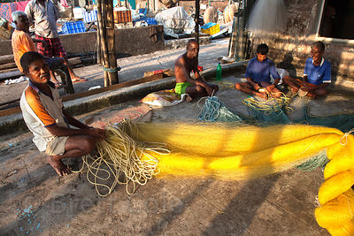 Men make fishing nets in the coastal village of Worli, Mumbai, India.