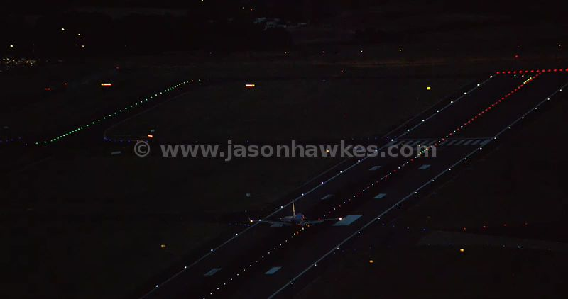 Aerial footage of an aeroplane moving along the runway at night