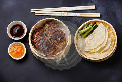 Peking Duck in bamboo steamer served with fresh cucumber, sauce and roasted wheaten chinese pancakes on black background