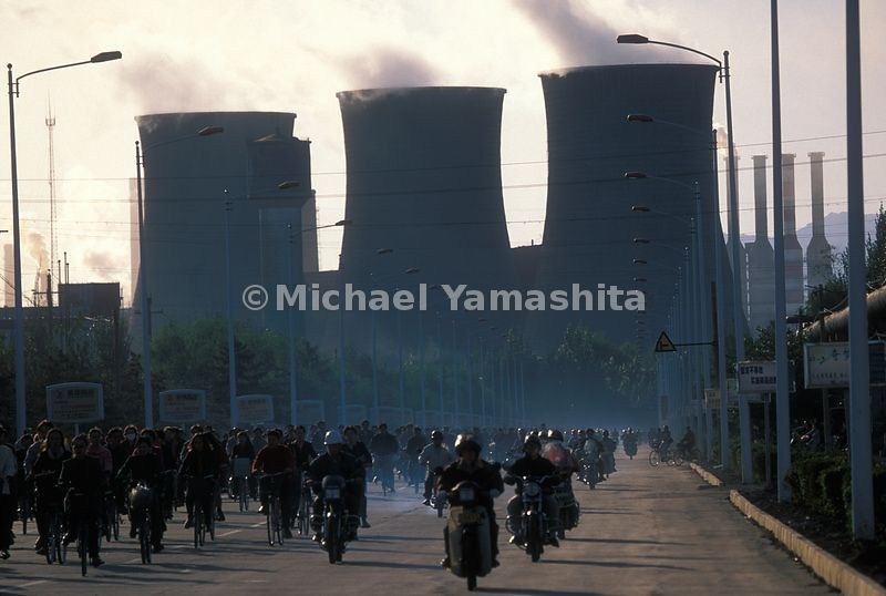 Rush hour in front of the steel factory in Baotou, China. The huge smokestacks of the factory loom in the distance.