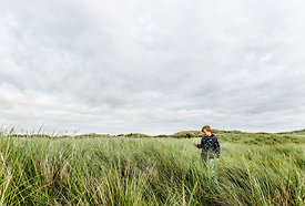 Boy with magnifying glass in Danish dunes