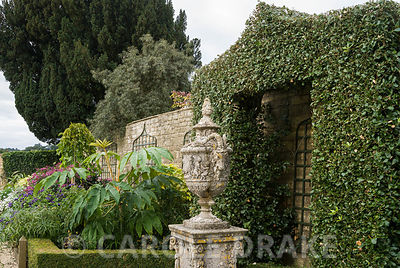 Shrub clipped into shape like a pointed arch frames a classical urn in the White Garden. Bourton House, Bourton-on-the-Hill, ...