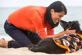Smiling Asian Woman on Beach Nose to Nose with Senior Dog