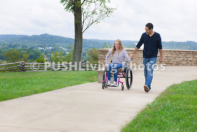 Young woman in a wheelchair with her boyfriend enjoying the views overlooking a river from a lookout.
