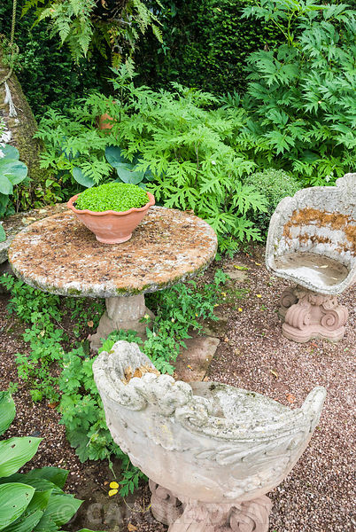 Stone chairs and table in the shade garden at Cothay Manor, Somerset