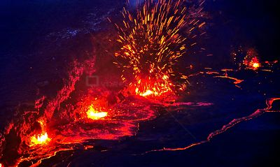 Eruption and molten lava flowing down the sides of the Erta ale volcano (the smoking mountain) in the Afar desert, Northern E...