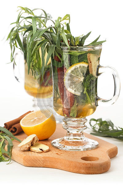 Tarragon hot drink tea with honey, lemon and cinnamon on white background