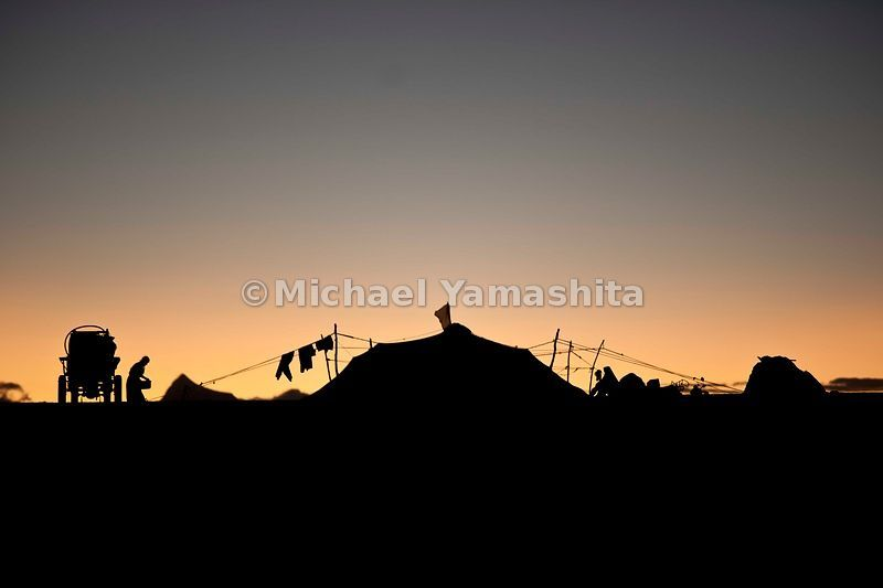 Silhouetted against an early morning sunrise, a Nomad encampment is situated along route 109, near the sacred Namtso Lake.