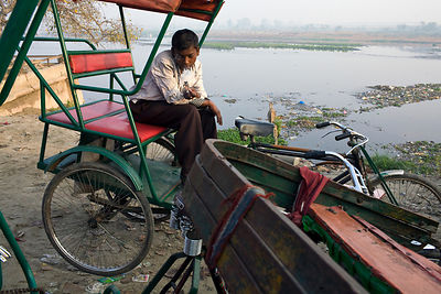 India - New Delhi - A homeless cycle rickshaw driver smokes a cigarette at a parking lot next to the Yamuna River where he sl...