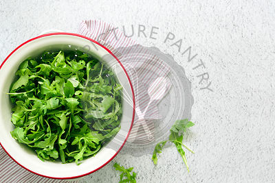 Fresh rocket leaves in a colander.