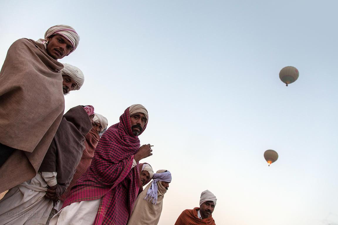 Hot air balloons are seen over the heads of a group of men at the Pushkar Camel Mela, Pushkar, Rajasthan, India.