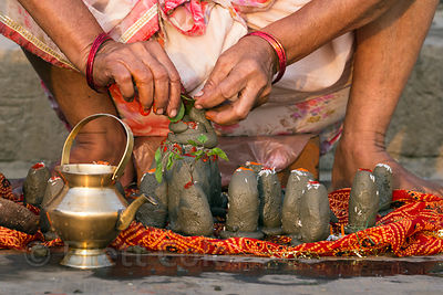 A woman crafts small mud scupltures adorned with flowers as part of a Hindu prayer, Assi Ghat, Varanasi, India