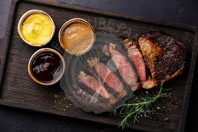 Sliced grilled Rib eye steak and three different sauces: Pepper sauce, Mustard and Barbecue on dark background close up