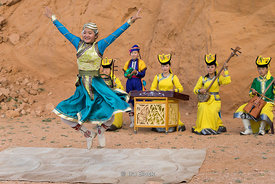 People dancing and playing mongolian music instruments at the Flaming Cliffs, Bayanzag, in the south Gobi desert, Mongolia.