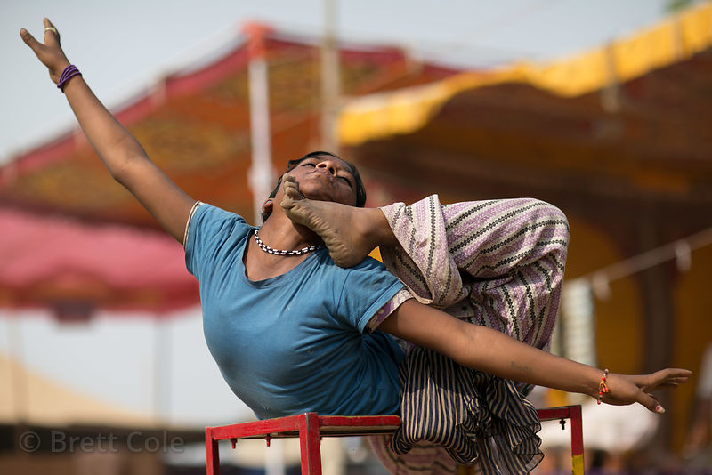 A dalit girl does a contortion act for no one at the Pushkar Camel Fair, Pushkar, Rajasthan, India. Such girls are deprived an education, make almost no money, and endanger their health with the routines they do. There wasn't even anyone watching.