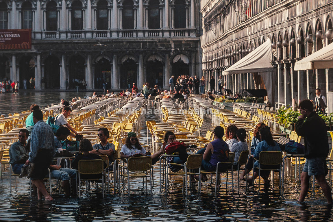 People relax in the chairs despite the flooding in front of the Procuratie in Piazza San Marco. Venice, Italy, October, 1993.