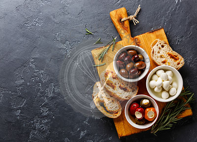 Olives, stuffed Peppers, mini Mozzarella cheese and sliced Ciabatta bread on dark background copy space