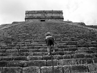 small boy climbs a pyramid at Chichen Itza