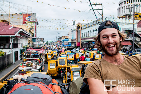 Happy man Riding The Roof Of A Jeepney In Heavy Traffic