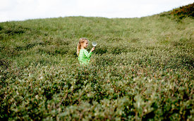 Girl with magnifying glass in Danish dunes 4