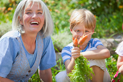 Germany, Bavaria, Mature woman and boy inspecting carrots in garden