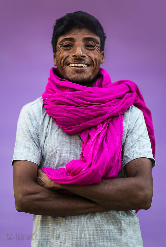 Portrait of a man on the street in Pushkar, Rajasthan, India. Candid with natural background (purple painted wall where the m...