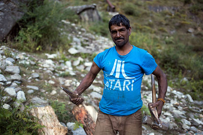 "A man wearing an ""Atari"" (video game company) t-shirt illegally cuts down trees for fuel wood on a slope above Vashisht, Mana..."