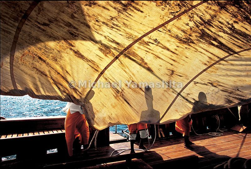 Sailors create their won form of shadow play, silhouetted by the sun on the Sanjeeda's sails, just off Lamu Island.