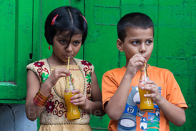 Sister and brother have a Mazaa mango drink during the Durga Puja festival, Beniatola, Kolkata, India