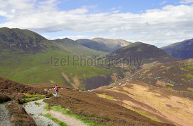 A hiker walking in the mountains of the English Lake District. Approaching Barrow Door with Outerside, Sail and Crag hill in ...
