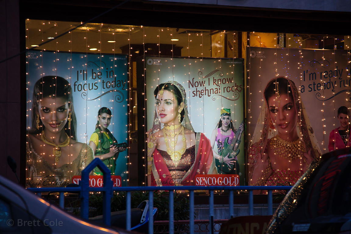 Christmas lights over large images of elegant women on a gold shop in Bowbazar, Kolkata, India.