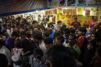 Crowds of beachgoers at Juhu Beach in Mumbai, India, wait out a monsoon squall in a market stall.