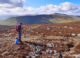 A hiker checking their position on a GPS map near the summit of Carrock Fell with views of Bowscale Fell and Blencathra in th...