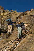 hikers climbing a chain ladder leading to the top of the amphitheatre, Drakensberg Mountain, South Africa