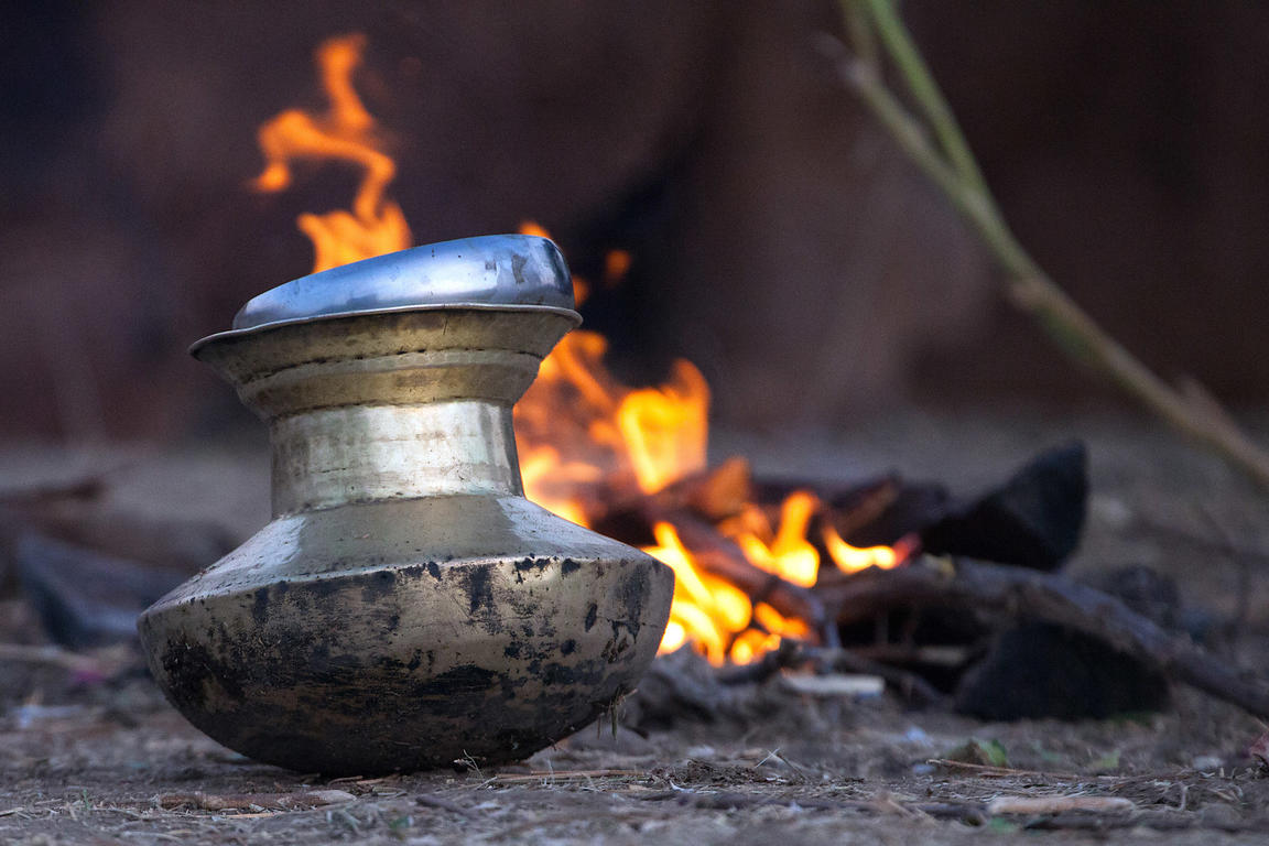 A metal water vessel sits in desert sand next to a campfire at the Pushkar Camel Mela, Pushkar, India.