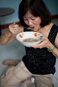 Vietnam - Ho Chi Minh City - A woman breakfasts on a dish of Pho noodle soup