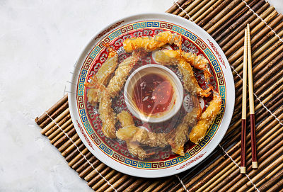 Deep fried breaded Tempura prawn shrimps with sauce on bamboo background