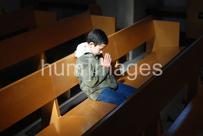 Little boy praying while sitting in empty church building