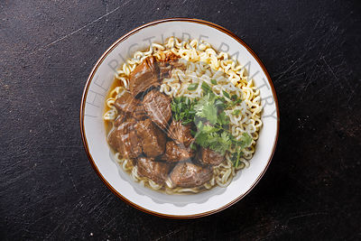 Slow cooked Beef meat with Asian noodles in broth on dark background