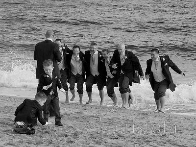groom and friends perform for wedding photographs  on the beach at Falmouth