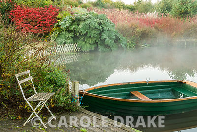 Early morning mist rises from one of the garden's lakes with rich red autumn colour provided by Euonymus alatus and the red s...