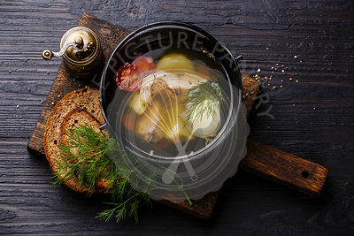 Fish soup with salmon, potato and carrot in black iron pot on black burned wooden background