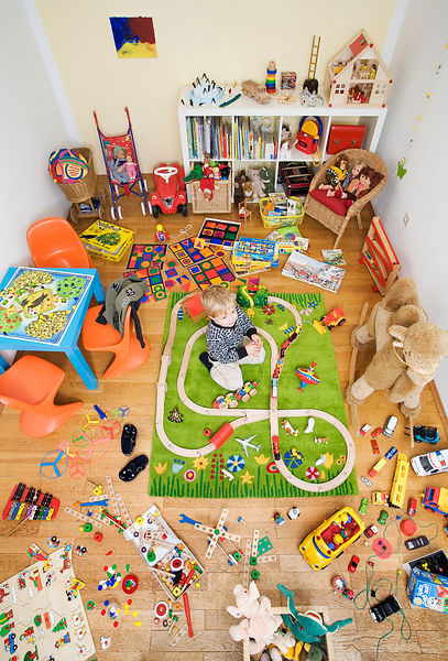Boy plays in room crowded with toys