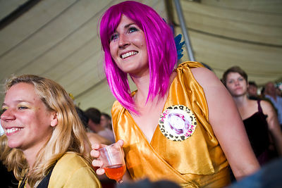UK - Standon - A woman in a purple wig with a drink smiles as she listens to a performer at the Standon Calling Festival