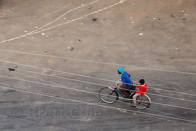 Distant overhead view of two boys riding a bike in Jaisalmer, Rajasthan, India