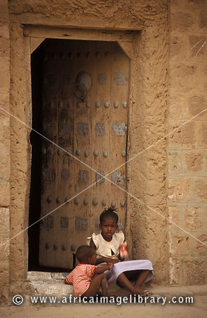 Children sitting in front of a traditional mud house with a Moroccan style door, Timbuktu, Mali